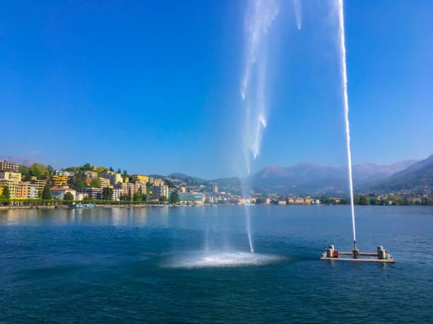 City and lake Lugano with fountain stock photo