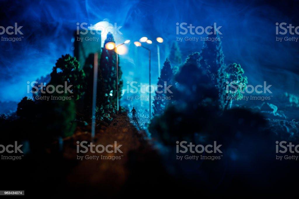 City at night in dense fog. Thick smog on a dark street. Silhouettes of man on road. Table decoration. Selective focus - Zbiór zdjęć royalty-free (Azerbejdżan)