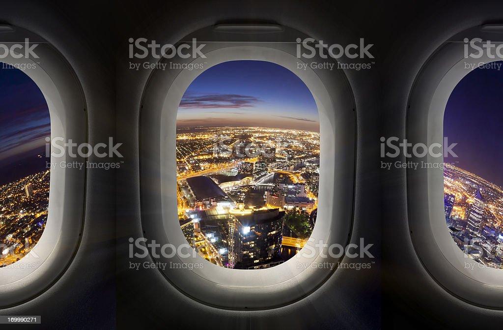 Ciudad de la noche a través de la ventana de avión - foto de stock