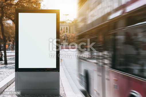 A tourist double-decker is passing by at a high speed near empty urban billboard mockup; two-decker full of tourists near the bus stop with the template of clean city information banner placeholder