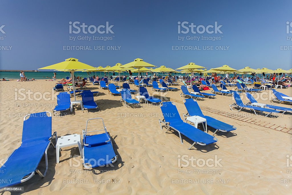 City beach with people and blue daybeds royalty-free stock photo