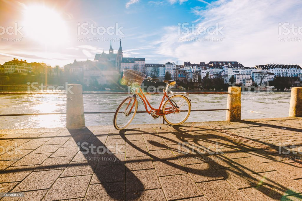 city bicycle with basket on the steering wheel of red color on the quay near the river Rhine in Switzerland against the backdrop of old city and authentic houses and cathedral on sunny day in winter stock photo