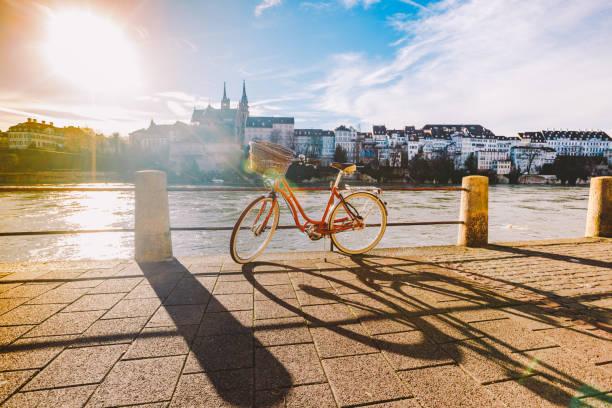 city-bike mit korb am lenkrad rote farbe auf dem kai in der nähe des rheins in der schweiz vor dem hintergrund der alten stadt und authentische häuser und kathedrale an sonnigen tag im winter - rhein stock-fotos und bilder