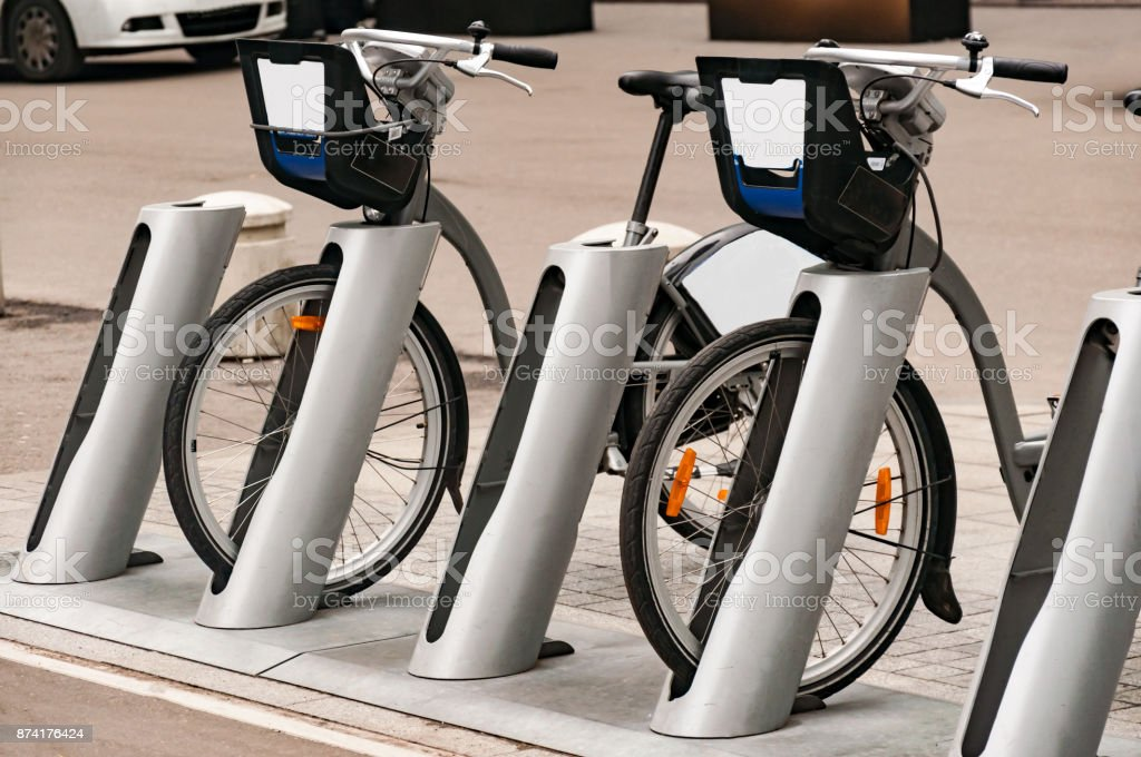 City bike rental system. Bicycle parts are large. Parking bicycles on city streets. With tinting and blurring. stock photo