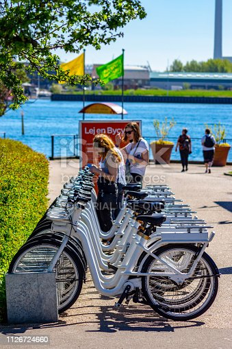 City bikes (Bycyklen) in docking stations in Copenhagen, Denmark. The bikes are available for short term hire by commuters or tourists and can be left at other docking stations around the city. There are two young women hiring bikes beside the harbour where the Little Mermaid statue is.