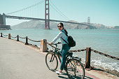 City biking Asian girl riding bike in town on summer day laughing with golden state bridge in background. Happy chinese woman outdoors cycling along the coast. urban lifestyle young lady smiling.