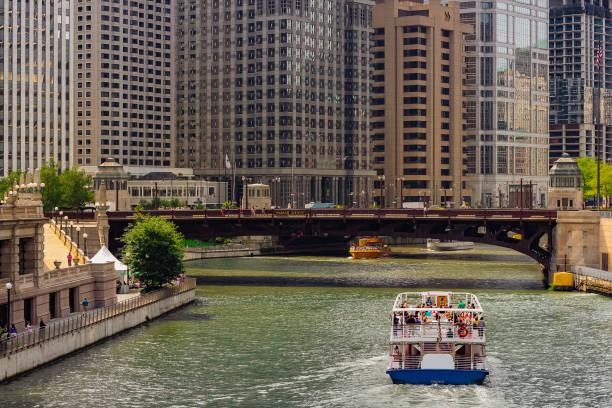 de gebouwen van de stad over de rivier van de chicago, illinois - rondvaartboot stockfoto's en -beelden