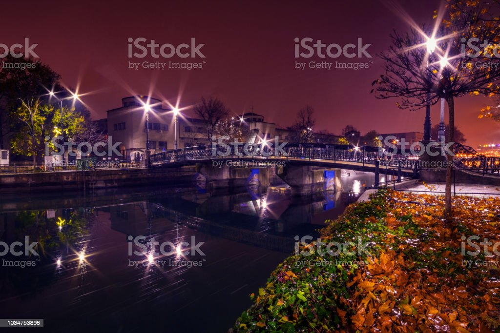 City by night with a bridge crossing a river and street lights in the autumn stock photo