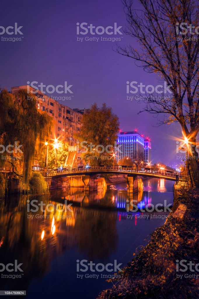 City by night with a bridge crossing a river with a modern building in the background stock photo