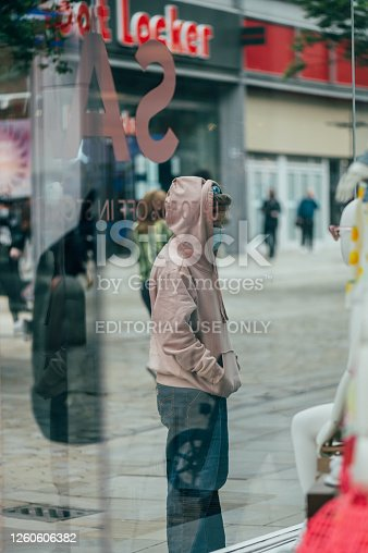 MANCHESTER, ENGLAND, UK - 24 JULY, 2020 City centre of Manchester, young girl in face mask is looking on shop displays