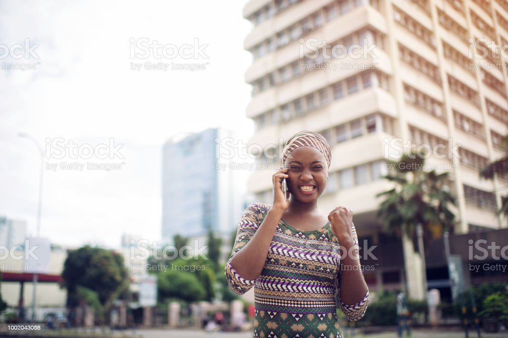 A young African girl talking on her mobile phone getting good news...