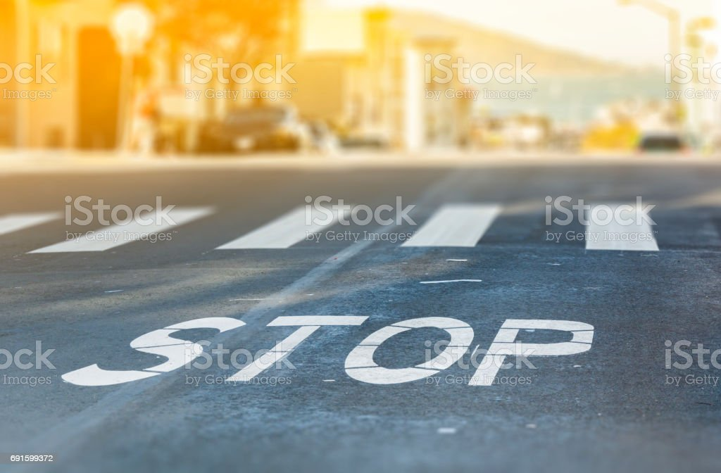 City crosswalk with symbol stop, closeup road texture with blurred San Francisco Bay in background in a warm sunny day stock photo