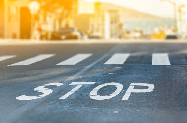 city crosswalk with symbol stop, closeup road texture with blurred san francisco bay in background in a warm sunny day - stop sign stock pictures, royalty-free photos & images