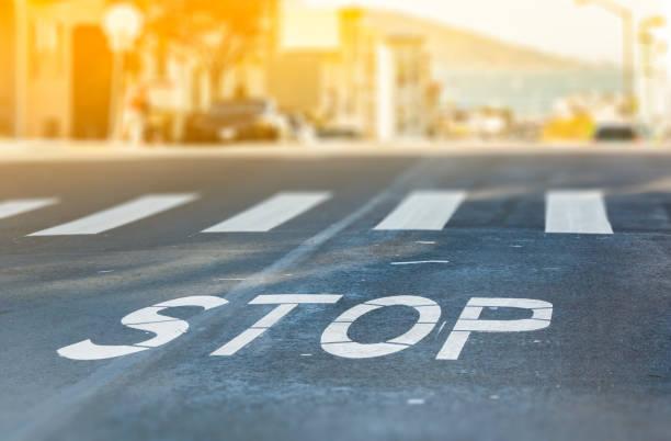 cruce peatonal de la ciudad con el símbolo stop, closeup textura camino borrosa bahía de san francisco en fondo en un día soleado caliente - stop sign fotografías e imágenes de stock