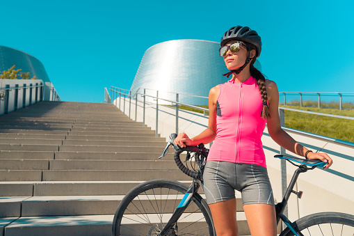 City cyclist woman with road bike wearing helmet, sunglasses, pink jersey for biking on hot summer day urban commute ride. Cycling concept.