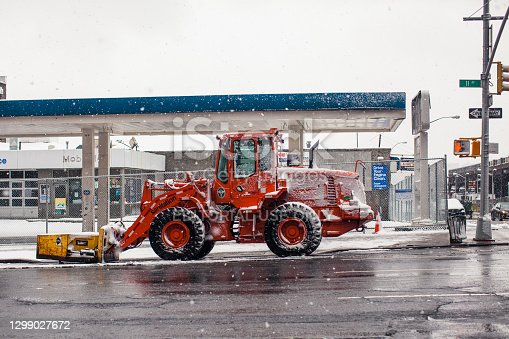 A large orange DSNY tractor stands on the road and is ready to go during a snow storm in New York City. The windows and hood of the tractor are covered with snow. Mobil gas station is on the background. In some places of the roadway, the snow has melted and puddles are visible. The traffic light enters the frame, pedestrians are prohibited from walking. Snow continues to fall and snowflakes are visible flying in the air. Winter storm in progress and snow gathers in drifts. Very bad weather. Mid day. March 21, 2018. NYC. Midtown Manhattan. New York. USA