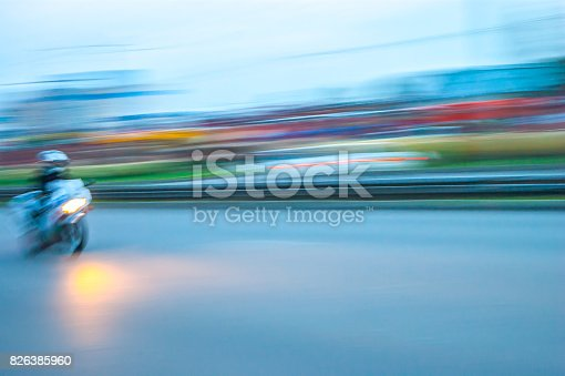 istock City evening rush hour with a motorcycle rider speeding along the street lights on, panning blurry vision 826385960