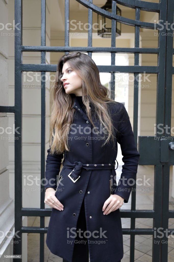 City fashion London Russian outdoor girl black outfit by gate stock photo