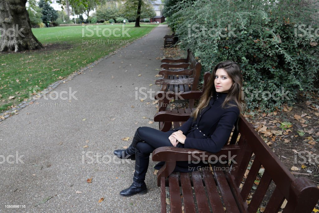 City fashion London Russian outdoor girl black outfit hands on lap stock photo