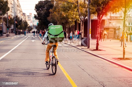 Delivery man food service courier on bicycle in town. Rear view of man riding a bicycle in the city street with green bag on back
