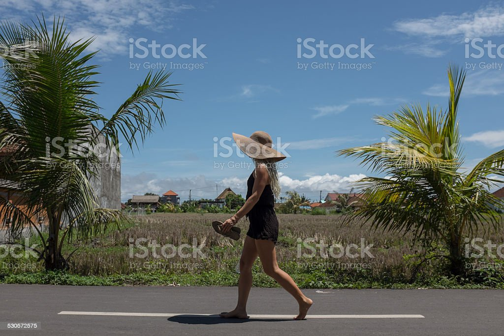 City girl barefoot walking along the road stock photo