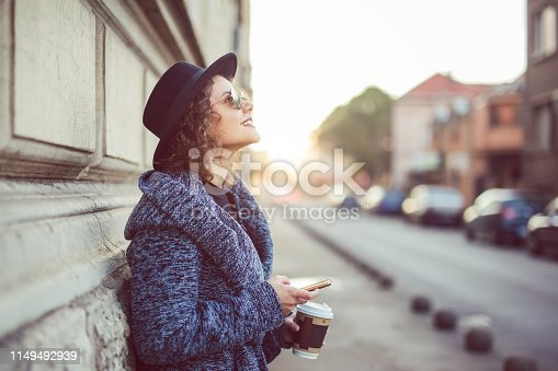 Young caucasian beautiful woman walking the street with coffee and her phone in her hands.