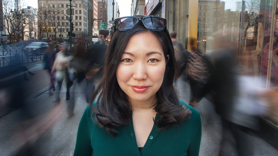 Beautiful young Asian woman standing on busy city sidewalk with people walking all around her. portrait close-up looking at camera.