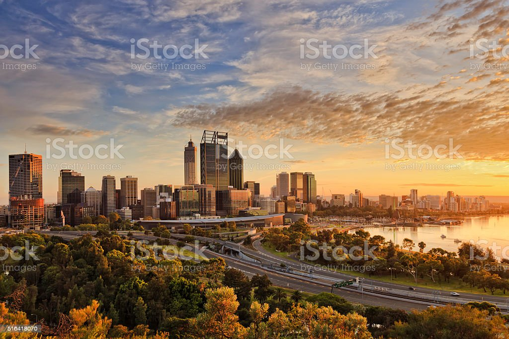 PERTH city gold light park Gold warm sun light litting CBD of Perth city as seen from Kings park with green trees and highway entering the city. Architecture Stock Photo