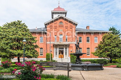 Frederick: City Hall in downtown city in Maryland with brick building exterior, sign and park square with flowers