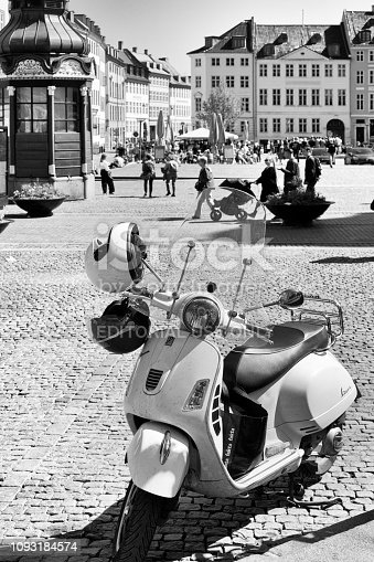City Hall Square, Copenhagen with a motor scooter in the foreground and tourists and locals in the background. It has been converted to black and white to invole a 60s feel to the image.