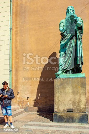 City Hall Square, Copenhagen statue of Moses outside Copenhagen Cathedral with a man looking at mobile phones in May 2018. In the foreground is a man on his mobile phone whilst the statue appears to contrast with the modern technology.