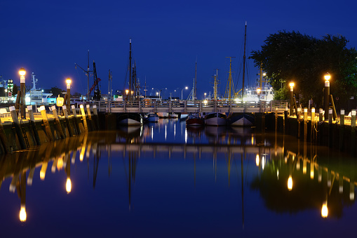 City harbour marina in Buesum, a German seaside resort and tourist destination at the north sea, blue hour night shot with many lights and copy space