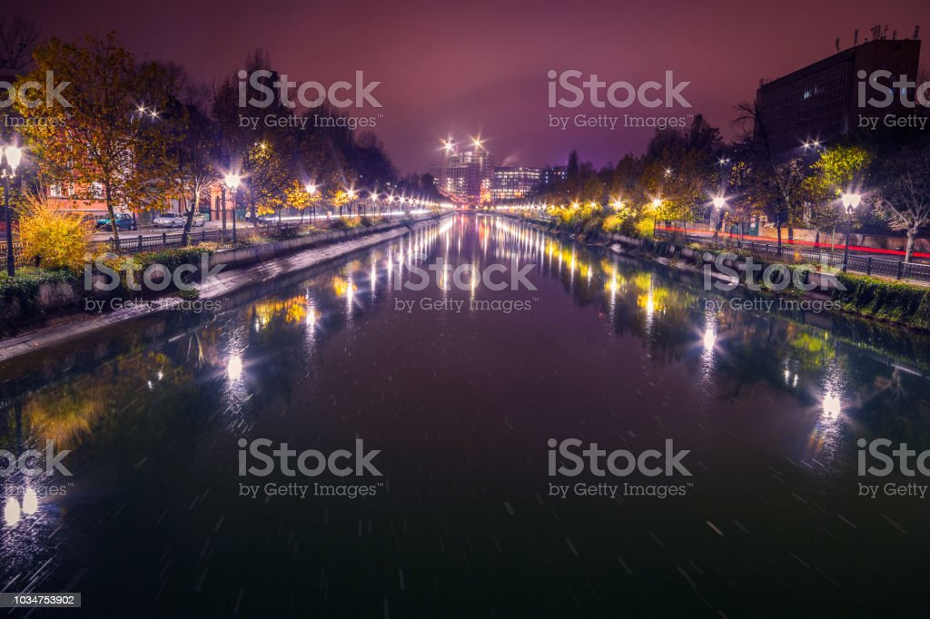 City in the night with a river and artificial lights in the autumn stock photo