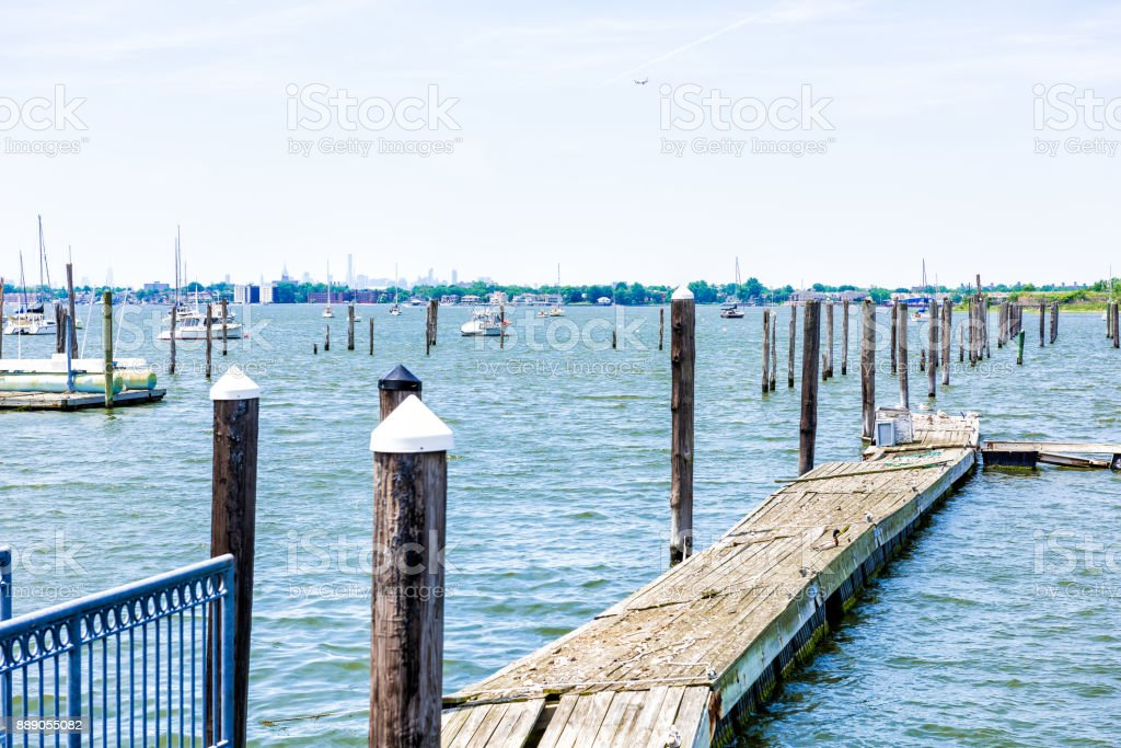 City Island harbor in Bronx, New York with boats and pier, Manhattan skyline or cityscape in distance stock photo