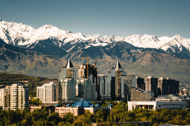 City landscape on a background of snow-capped Tian Shan mountains in Almaty Kazakhstan City landscape on a background of snow-capped Tian Shan mountains. The complex of buildings along Al-Farabi avenue. Photo taken in Almaty, Kazakhstan. kazakhstan stock pictures, royalty-free photos & images
