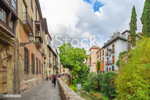 istock City landscape. View of the street and the old stone bridge over the Darro River. Granada, Andalusia, Spain 1282993653