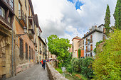 Granada, Andalusia / Spain - September 13, 2019: City landscape. View of the street and the old stone bridge over the Darro River. Granada, Andalusia, Spain