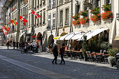 Bern Switzerland - September 14, 2018: Life is going on near the medieval tenement houses with arcades on the main street and pedestrian zone in the centre of this capital city. The City of Bern is one of the countless great places in Switzerland and it is the political centre of this Country. Numerous museums, a wide cultural offer, a variety of tourist attractions makes it a travel destination for tourists from all over the world.
