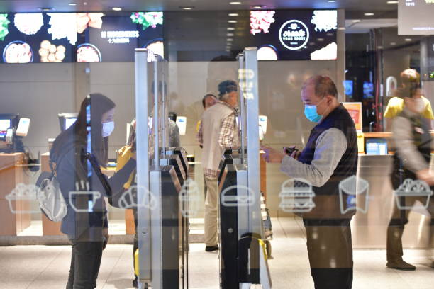 City life in Hong Kong amid pandemic March 25, 2020, Hong Kong: People with face masks are seen ordering food at self-ordering kiosks in a restaurant in Admiralty, Hong Kong, amid the Coronavirus outbreak. amid stock pictures, royalty-free photos & images
