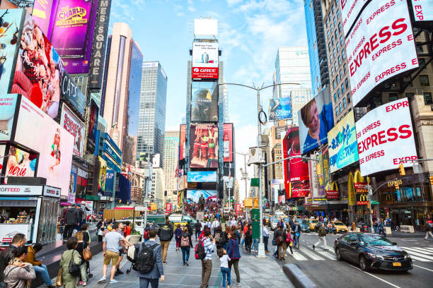 city life in times square at daytime. - times square stock photos and pictures