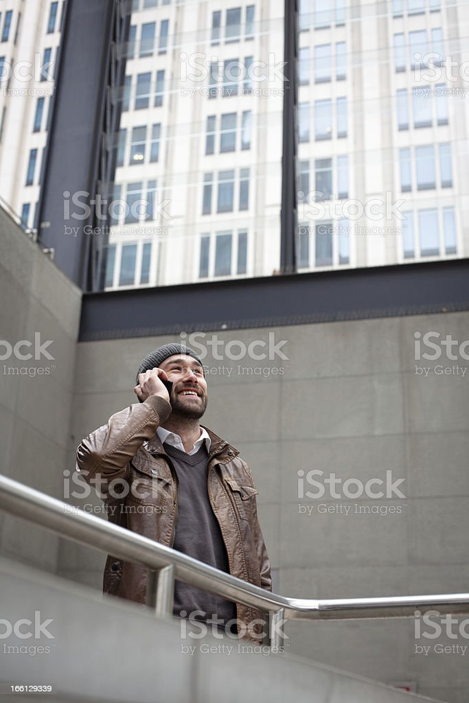 city life: laughing casual Man at phone in modern architecture royalty-free stock photo