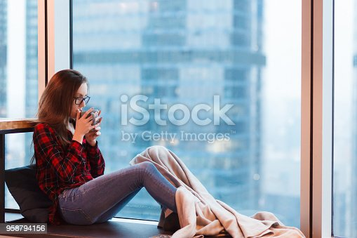 1162297213 istock photo City life - young charming girl - office manager - sits under blanket and drinks coffee looking from large window overlooking a blurry skyscraper 958794156
