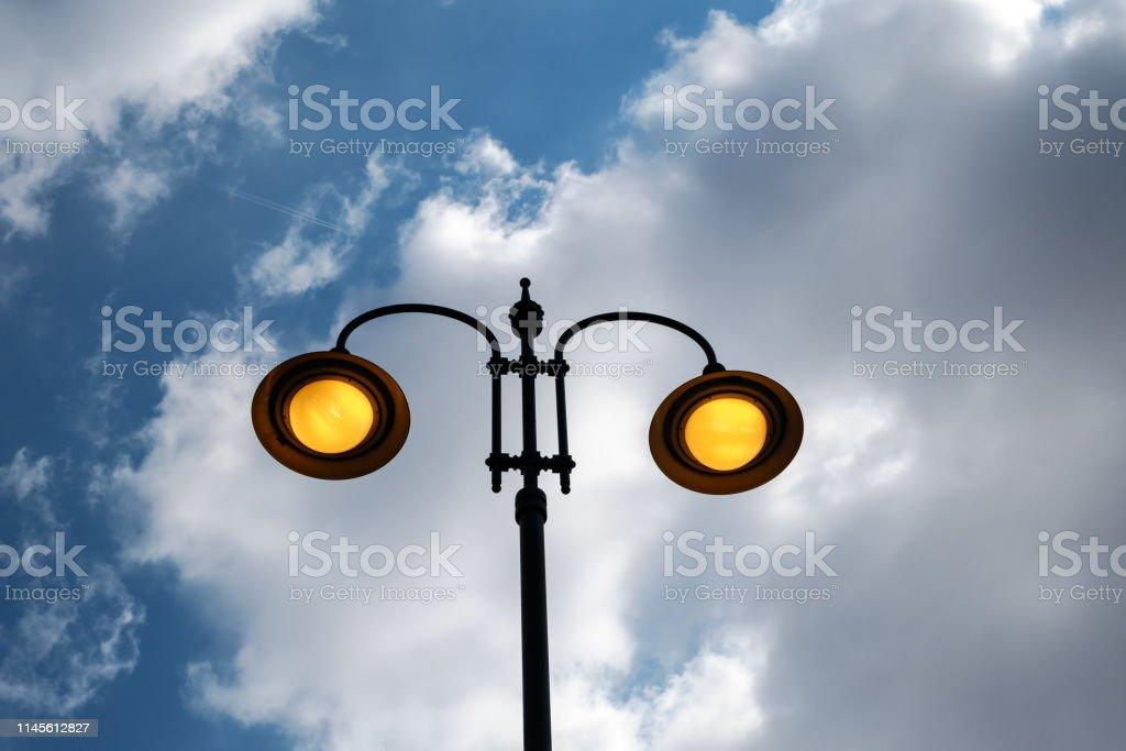 city lit light pole on day with cloudy sky