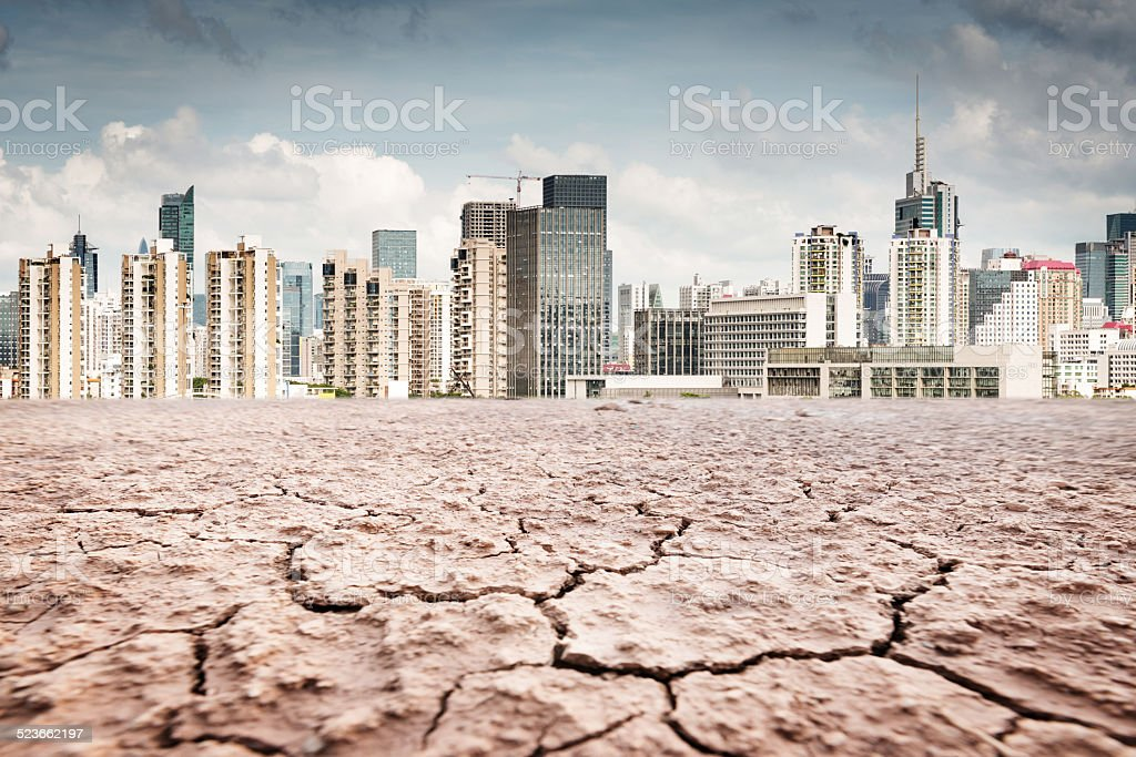 city looks over a cracked earth landscape stock photo