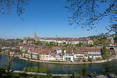 Bern, Switzerland - April 21, 2017: The Old Town buildings in the distance and the visible waters of the Aare River. This is one of the countless wonderful places in Switzerland, which is a tourist attraction often visited by many tourists from all over the world.