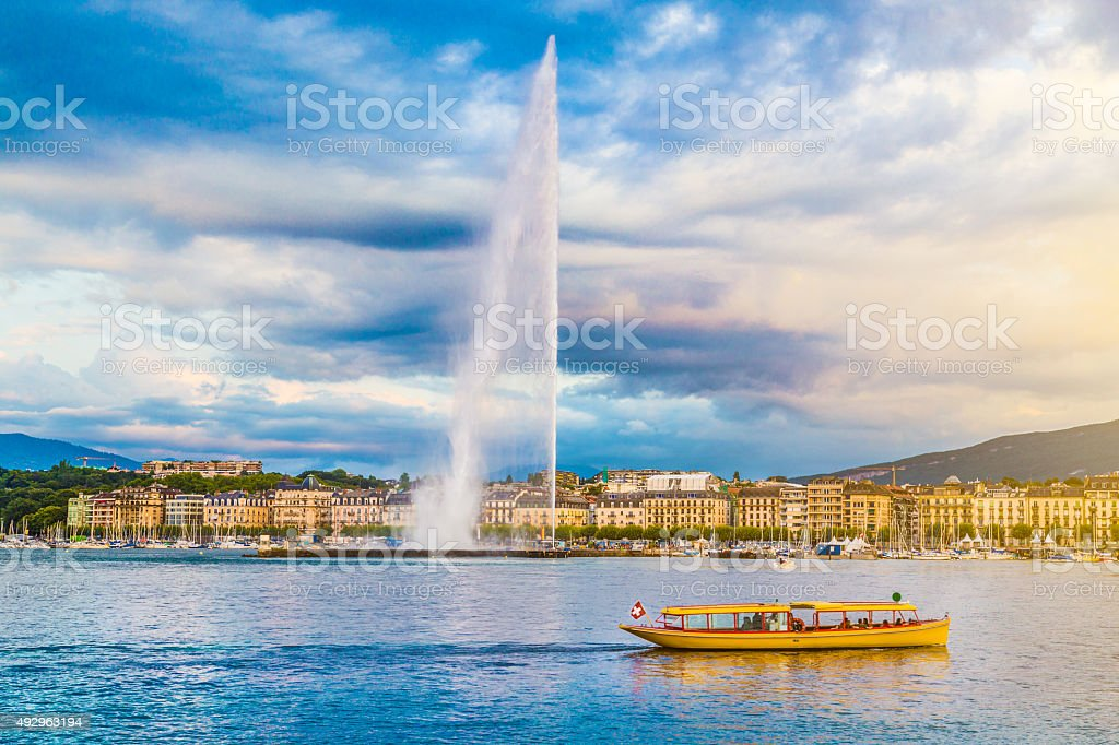 City of Geneva with Jet d'Eau fountain at sunset, Switzerland Beautiful view of Geneva skyline with famous Jet d'Eau fountain at harbor district in beautiful evening light, Switzerland. 2015 Stock Photo