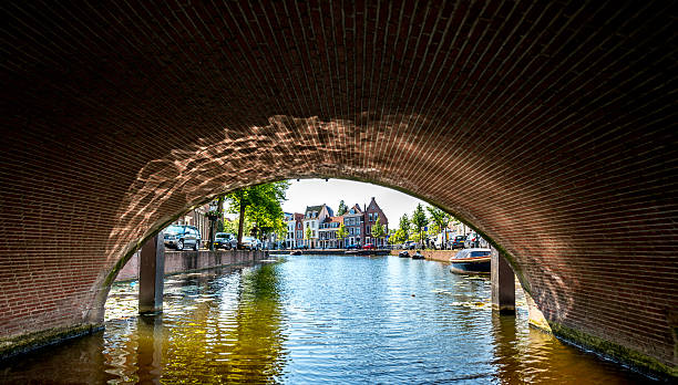 City of Leiden with his canals in early morning sun. Shot from the water, under a bridge view on the Rapenburg leiden stock pictures, royalty-free photos & images