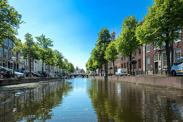 City of Leiden with his canals in early morning sun. Shot from the water, view on the Rapenburg leiden stock pictures, royalty-free photos & images
