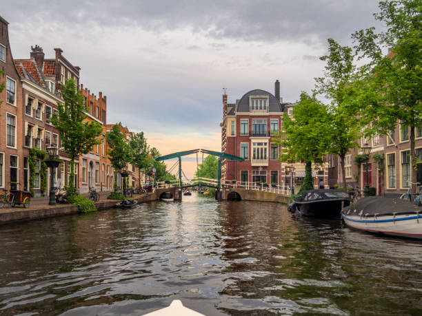 City of Leiden with his canals in early morning sun.This image is GPS tagged Shot from the water, view on the Old Rijn, Leiden, the Netherlands canals with historical houses in the dutch city of Leiden. Birthplace of Rembrandt van Rijn. leiden stock pictures, royalty-free photos & images