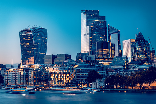 City of London's financial district and Tower of London famous landmark and tourist attraction during late hours of the day with its evening illumination as photographed from London's City Hall. Long exposure technique used to blur the river Thames high tide waters reflecting the city lights and nautical transportation ferries. Shot on EOS R full frame system with premium RF lens for highest quality and high resolution. Blue toning added in post production.